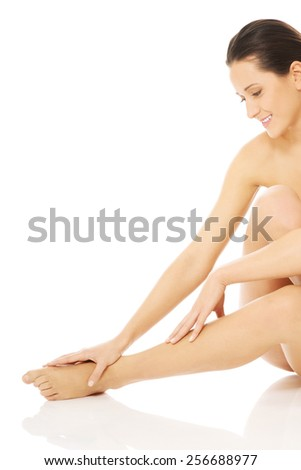 Nude woman sitting on the floor and touching her feet