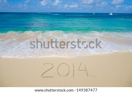 Number 2014 on the sandy beach - concept holiday