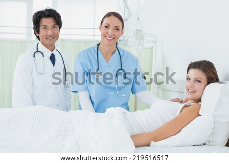 Nurse and doctor checking patient while looking at camera