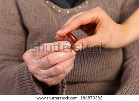 Nurse giving a pill to an  elderly wrinkled hand
