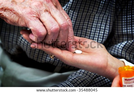 nurse giving senior man pills