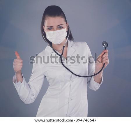 Nurse in robe is holding a stethoscope against of grey background