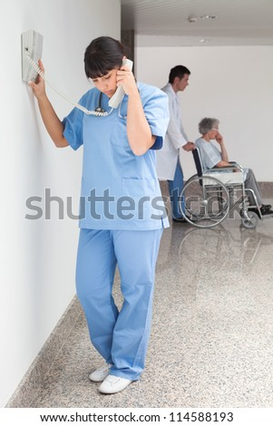 Nurse on telephone in hallway while doctor pushes patient in wheelchair