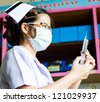Nurse with medical syringe with needle in ampule getting ready for patient injection - stock photo