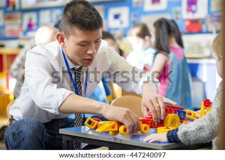 Nursery teacher is helping one of his students to make a car with building blocks.