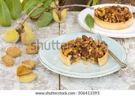 nuts, almonds and caramel tart, on a rustic background in the almond ...