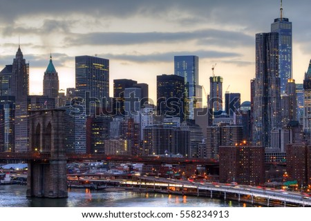 NYC skyline at sunset with the night lights of the downtown skyscrapers and the Brooklyn Bridge in Manhattan, New York City