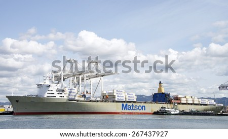 OAKLAND, CA - APRIL 06, 2015: Matson Cargo Ship MANOA loading at the Port of Oakland. Tugboat POINT VINCENTE with a barge ship pushed up next to the vessel to assist with maritime services.