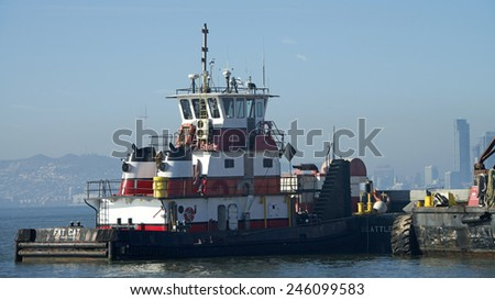 OAKLAND, CA - JANUARY 21, 2015: Tugboat FAT CAT assisting Manson Construction Dredge ship DREDGE NJORD navigate the water around the Port of Oakland to complete it's dredging and maintenance work.