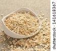 Oat flakes in white ceramic bowl on sackcloth background - stock photo