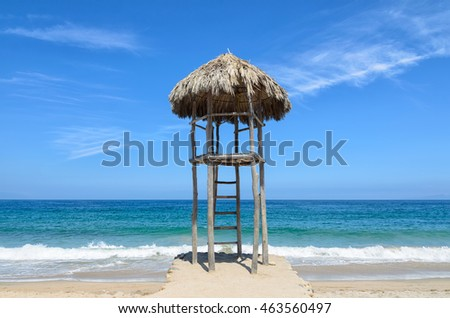 Observation post covered with dry palm leaves at the beach