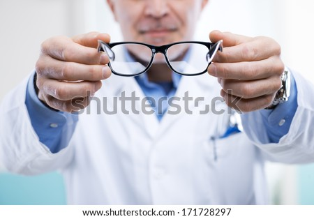 Oculist giving a pair of glasses during a visit.