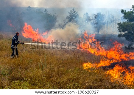 Odessa, Ukraine - August 4, 2012: Severe drought Fires destroy forest and steppe. Firefighters in protective clothing quenched with water from hydrants pockets fire, August 4, 2012 in Odessa, Ukraine.