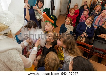 Odessa, Ukraine - December 22, 2016: Children's Christmas New Year's concert. Children play with Snow Maiden and Santa Claus. Emotional bright children's show in elementary school
