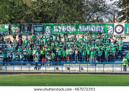 ODESSA, UKRAINE - September 21, 2016: Football fans and spectators in stands of the stadium emotionally support their team. Hooliganism and firecrackers in stands. Violation of rules of game