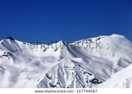 Off piste snowy slope and blue clear sky. Caucasus Mountains, Georgia, ski resort Gudauri.