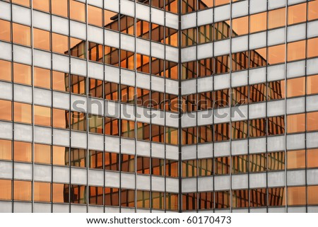 office building reflected in the warm orange windows of another office building
