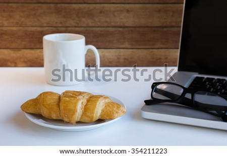 Office desk with glasses on computer, Croissant and coffee mug ,wood background
