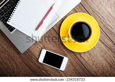 Office desk with laptop computer, notebook, mobile smartphone and coffee cup.