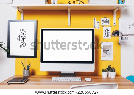 Office workplace with computer./ Modern creative workspace on yellow wall.
