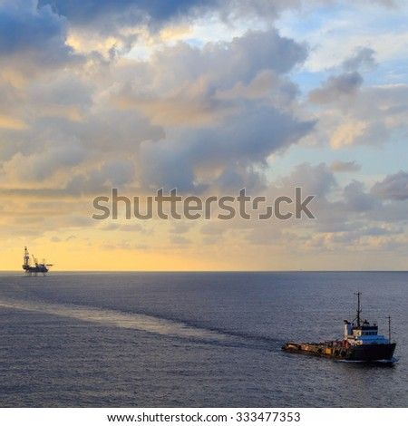 Offshore jack up drilling rig and supply boat in the middle of the ocean during sunset time