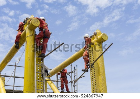 Offshore workers complete with falling protection working at height.