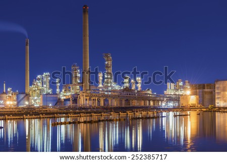 Oil refinery at twilight - petrochemical industry with water reflect.