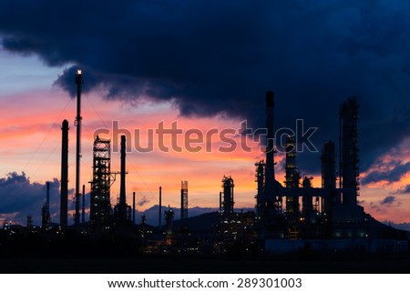 Oil refinery factory in silhouette at sunrise with dark cloud