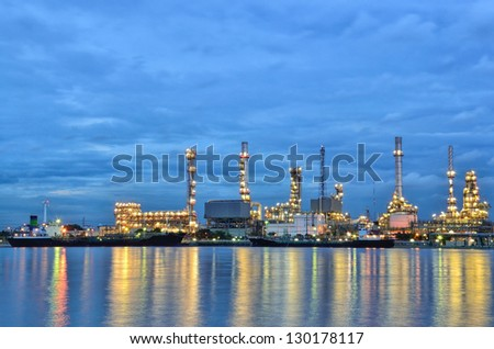 Oil refinery factory with reflection on the river in Bangkok, Thailand.