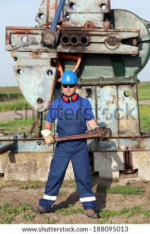 oil worker with pipe wrench posing