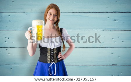 Oktoberfest girl smiling at camera holding beer against painted blue wooden planks