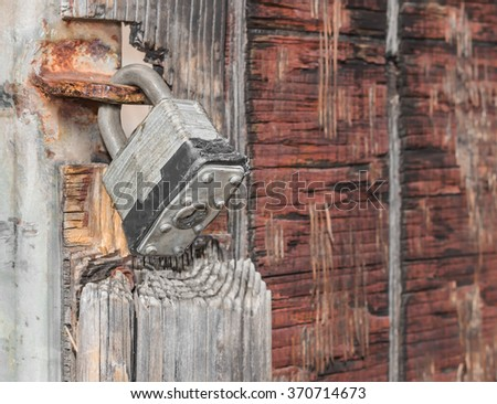 Old and worn metal padlock locking hanging on grungy wooden gate. Blurred background with copy space. Rust and brown colors. Rough texture.