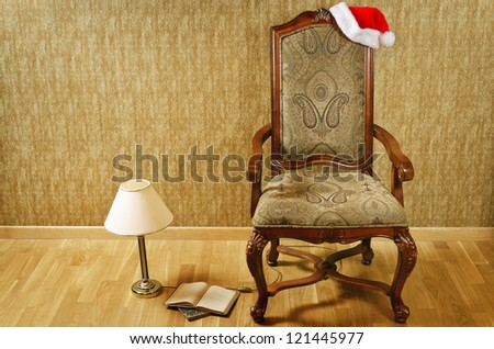Old armchair with Santa hat and a lamp with a book near it