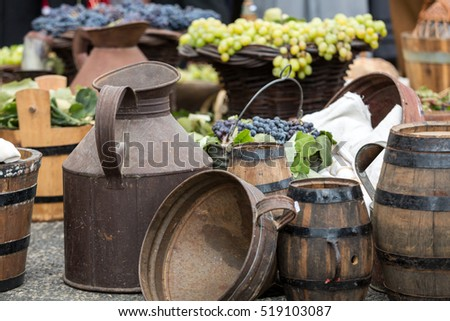 old barrels and tools for wine production and  baskets with grapes