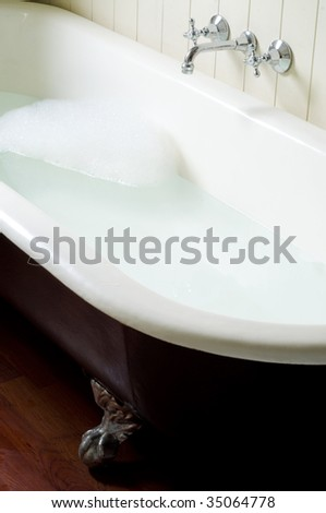Old bath tube with bubbles, water and hot and cold tap