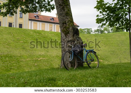 Old bicycle near the medieval castle. Nesvizh, Belarus. Focus on bicycle and an old tree