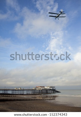 Old biplane flying over the pier and beach at Cromer on the Norfolk coast in South East England