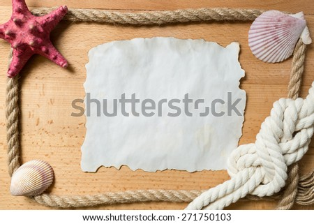 Old blank piece of paper with frame of ropes and seashells