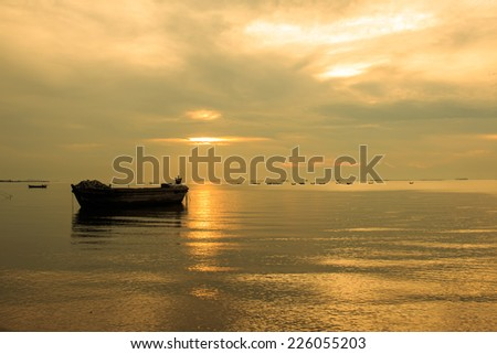 old boat in front of sunset background in golden color tone