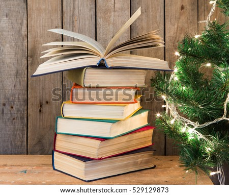 Old books and Christmas tree on the wooden background