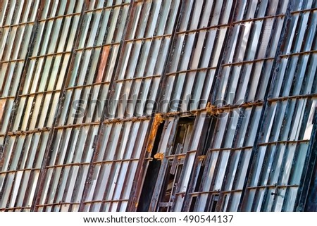 Old broken stained glass windows on facade of abandoned damaged vintage industrial building with factory interior wreckage close up detail exterior architecture theme background view