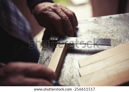 Old carpenter taking measurement of a wooden plank, retro tinted