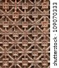Old Carved wooden latticework with flowers and squares design creating a perforated wall. - stock photo