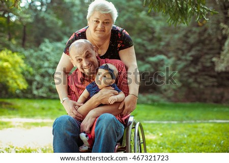 Old couple holds their little grandchild while standing in the park