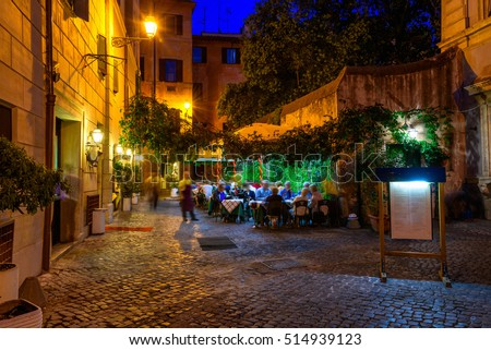 Old cozy street at night in Trastevere, Rome, Italy. Trastevere is rione of Rome, on the west bank of the Tiber in Rome, Lazio, Italy.  Architecture and landmark of Rome. Nightlife of Rome.