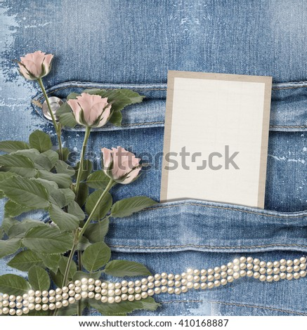 Old denim background with paper frame, pearls and pink roses