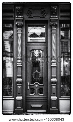 old door, black and white monochrome image, architecture background. NOISE AND CONTRAST intentionally added for a retro photo effect