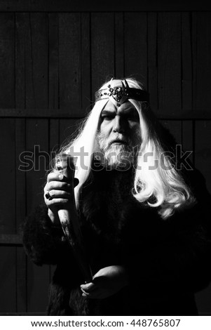 old druid bearded man with long beard on serious face and hair in fur coat and crown with gem stones jewellery on wooden background holding animal antler or horn, black and white