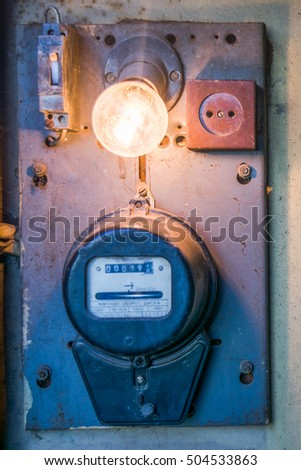 Old electric meter with a bulb lamp, a fuse and a wall outlet in old garage