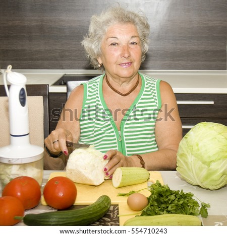 Old European woman cooking vegetables in kitchen.